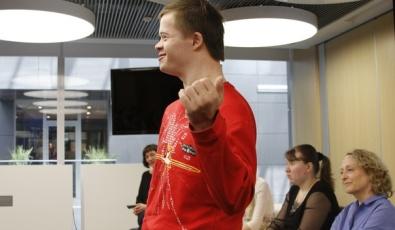 """Участник программы фонда """"Лучшие друзья"""" Витя Бодунов улыбается, рассказывая что-то аудитории, за его спиной сидят также перед зрителями на стульях сидят Аня Арефьева и Денис роза."""