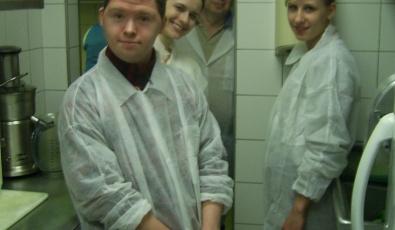 """Участники Дима, Кристина, куратор поддерживаемого трудоустройства Маруся и папа Димы в белых халатах на кухне пиццерии """"Папа Джонс"""" позируют перед фотокамерой."""
