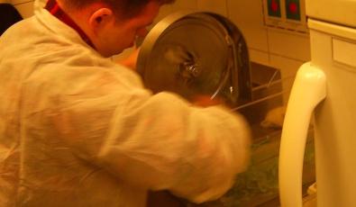 """Участник программы фонда """"Лучшие друзья"""" Дима моет приспособление для резки овощей в белом фартуке на кухне пиццерии """"Папа Джонс"""""""